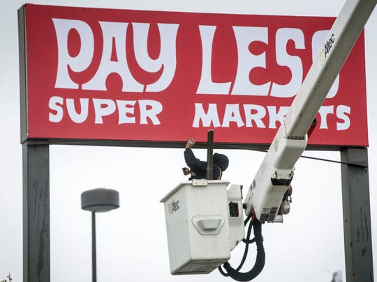 A crew finishes the sign promoting the Pay Less supermarket