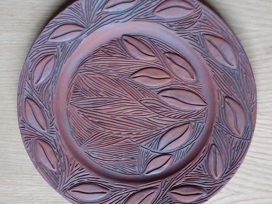 """Ceramic wall platter by Lynn LaLuzerne, part of """"The Garden: An Artist's Interpretation"""" at the Miller Art Museum."""