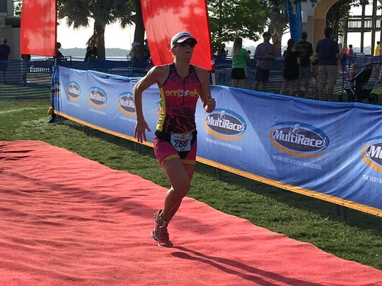 Megan Campbell, seen hear finishing in the Tri Cocoa Beach in May, likes training during the heat of the day during the summer.