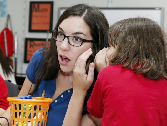 Trinity Sorrels, 8, tells a secret to Chelsea Fiske, left, a New Hope volunteer, during a New Hope after-school session in Tulsa, Okla., Wednesday, Oct. 21, 2015. New Hope Oklahoma offers after-school programs, weekend retreats and overnight summer camps that annually serve about 500 children who have a parent in prison. (AP Photo/Sue Ogrocki)