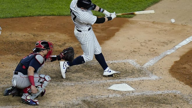 New York's Clint Frazier hits a two-run double as Red Sox catcher Christian Vazquez watches during the seventh inning Friday night in New York.
