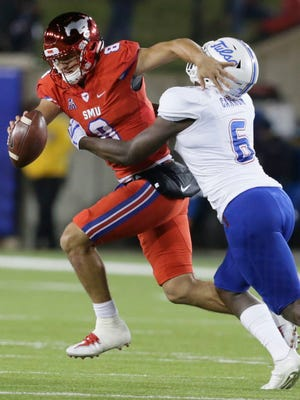 SMU quarterback Ben Hicks (8) is wrapped up by Tulsa linebacker Diamon Cannon (6) during the first half.
