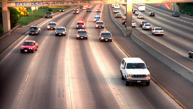 FOR USE SUNDAY, JUNE 8, 2014, AND THEREAFTER- In this June 17, 1994 file photo, a white Ford Bronco, driven by Al Cowlings carrying O.J. Simpson, is trailed by Los Angeles police cars as it travels on a Southern California freeway in Los Angeles. Cowlings and Simpson led authorities on a chase after Simpson was charged with two counts of murder in the deaths of his ex-wife, Nicole Brown Simpson, and her friend, Ron Goldman. (AP Photo/Joseph Villarin, File) ORG XMIT: NY881