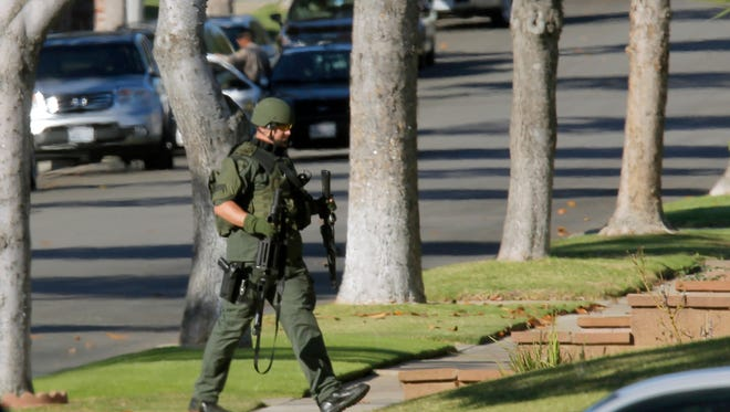 An Inglewood, Calif., police officer moves into position outside a residence on Wednesday in Inglewood, Calif., where a police officer was shot and another received minor injuries in a confrontation with a gunman who barricaded himself inside a home, authorities said.