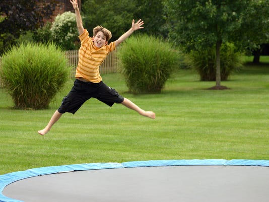 A small child jumping on a trampoline