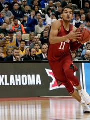 FILE - In this March 15, 2018, file photo, Oklahoma's Trae Young drives to the hoop during overtime of an NCAA men's college basketball tournament first-round game against Rhode Island,in Pittsburgh. Young is a member of the Associated Press NCAA college basketball All-America first team, announced Tuesday, March 27, 2018.(AP Photo/Keith Srakocic, File)