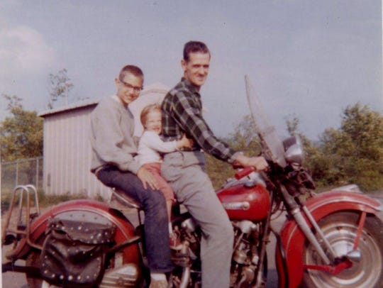 Donald Major (front) drives his motorcycle with his