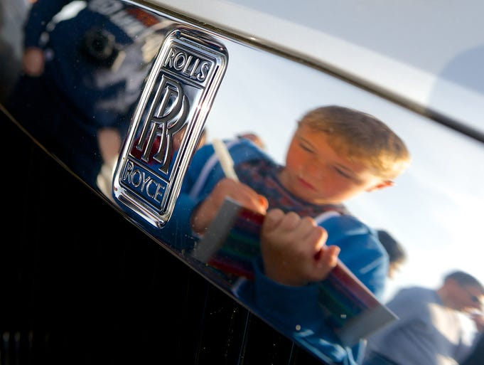 A boy is reflected in the famous radiator of a Rolls-Royce