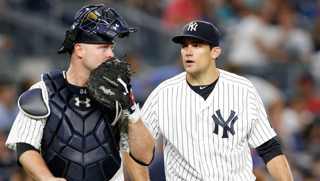 New York Yankees catcher Brian McCann, left, talks tostarting pitcher Nathan Eovaldi during the fifth inning of a baseball game against the New York Mets, Thursday, Aug. 4, 2016, in New York. Eovaldi gave up two home runs in the inning.