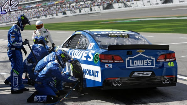 Jimmie Johnson's crew works on his car during a pit stop in the NASCAR Clash auto race at Daytona International Speedway, Sunday, Feb. 19, 2017, in Daytona Beach, Fla. (AP Photo/John Raoux)
