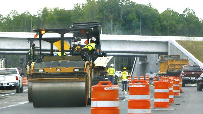 Construction workers work to lay asphalt on State Road 100 near the overpass of the new bypass in Starke last fall.  Workers are set to soon begin work on a railroad overpass on the highway in downtown