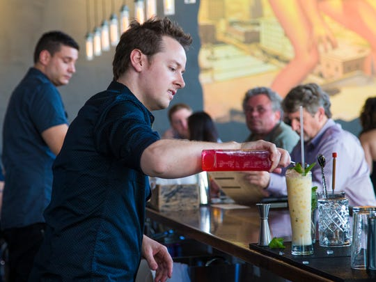 Ross Simon, owner of Bitter & Twisted Cocktail Parlour, mixes a drink at the downtown Phoenix bar last month.