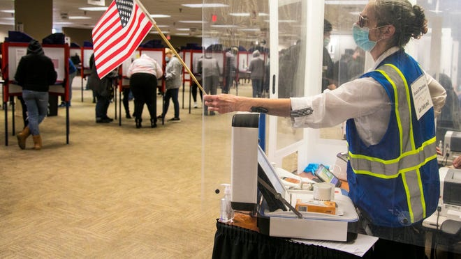 Lois VonHandorf, a Hamilton County Board of Elections worker, waves her flag to let the next voter know she's available for check-in, Sunday, Nov. 1, 2020.