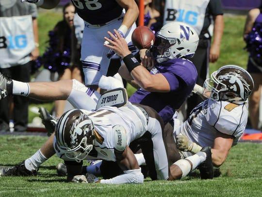 Northwestern quarterback Clayton Thorson (18) fumbles