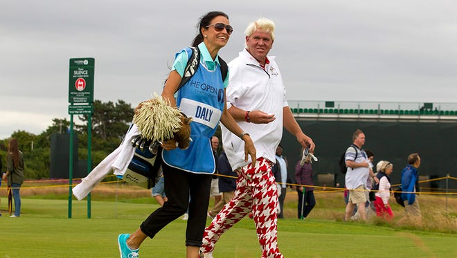 John Daly laughs as he walks down the 17th fairway with Anna Cladakis during a practice round at the Royal Liverpool Golf Club prior to the start of the British Open Golf Championship, in Hoylake, England in 2014.