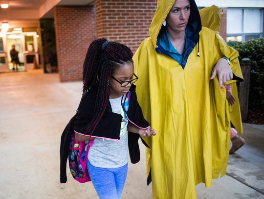 Tymia Dean is escorted to her car by teacher Jessica