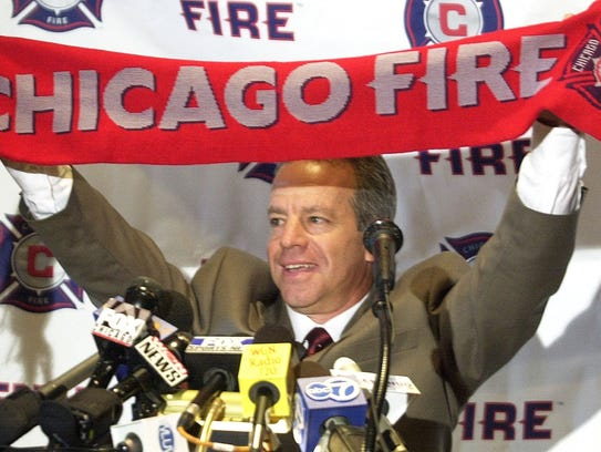 Dave Sarachan holds up a Chicago Fire scarf on  Monday,
