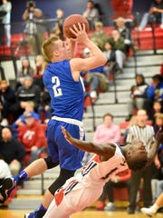 Cedar Crest's Blake Thomson draws a charge as he goes for two against Cedar Jahill Young.