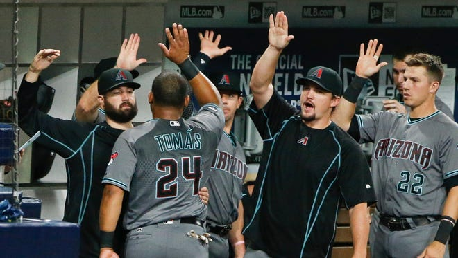 Arizona Diamondbacks' Yasmany Tomas high-fives his way through the dugout after scoring against the San Diego Padres during the second inning of a baseball game Friday, Aug. 19, 2016, in San Diego.