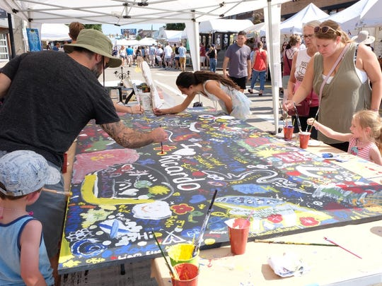 Attendees of the Ferndale DIY Festival contribute to a free-hand community painting on Sept. 23.