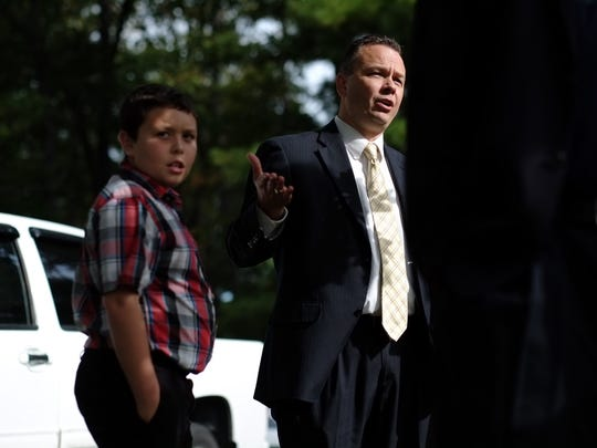 White supremacist, Thomas Robb, son to Pastor Thomas Robb, speaks with media alongside his son Caleb Robb, 11 at the Stormfront summitt in Crossville on Saturday, Sept. 30, 2017.