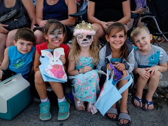 Kids with painted faces wait along Huron Avenue before