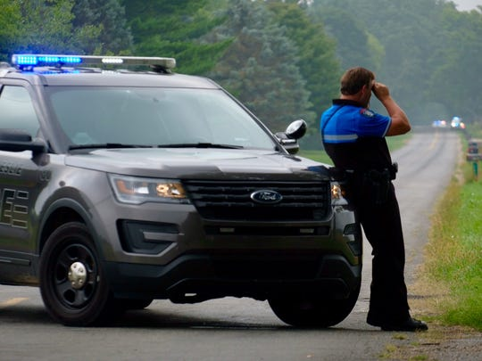 A Leslie police officer blocks Edgar Road just south of Harper Road near Mason and uses binoculars to scan the fields for an armed man Sunday, Aug. 26, 2018.