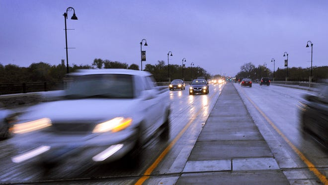 Cars are a blur as they whiz along the new Granite City Crossing at dusk.
