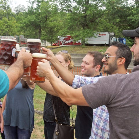 Friends raise their beer glasses for a toast as...