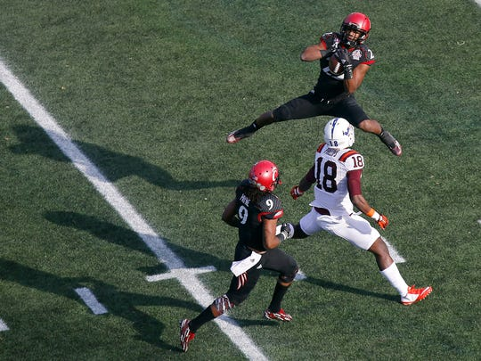 Bearcats safety Zach Edwards leaps to intercept the ball over Virginia Tech wide receiver Cam Phillips in the first quarter.