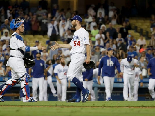 Los Angeles Dodgers pitcher Tony Cingrani, right, and catcher Yasmani Grandal celebrates their win against the Chicago White Sox during a baseball game in Los Angeles, Tuesday, Aug. 15, 2017. (AP Photo/Chris Carlson)