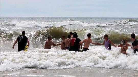 People form a human chain to search for a boy missing at Grand Haven State Park Sunday, July 20, 2020.