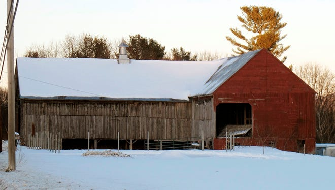 In this Feb. 27, 2015 photo, the barn where Orville Gibson disappeared on the morning of New Year's Eve 1957 sits alongside on U.S. Route 5 in Newbury, Vt. Almost 60 years after he disappeared and was later found dead, a retired Vermont judge is arguing in a new book that Gibson's death was a suicide. For decades many thought Gibson's death was vigilante revenge for his beating of a hired man. But Gibson's surviving relatives still believe he was murdered and there could be people in town who know who did it.