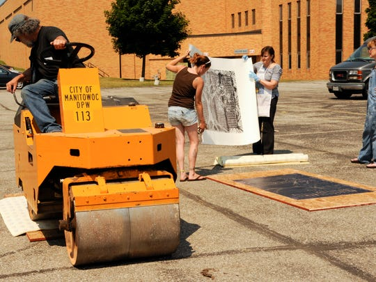 From 2014 event: from left, event organizer Berel Lutsky operates the steamroller as he presses a large-scale print as volunteer Tiffany Graubner of Manitowoc helps artist/printmaker Judith Joseph of Northbrook, Illinois, lift up her large-scale 60-inch-by-36-inch relief print after it was steamrolled with help from assistant Ruti Modlin of Chicago.