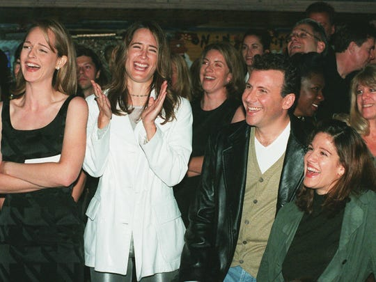 """In this Nov. 11, 1996, file photo, """"Mad About You"""" cast members Helen Hunt, from left, Anne Ramsay, Paul Reiser and Reiser's wife Paula laugh at a satiric video made by the show's crew during a private party at the House of Blues in West Hollywood, Calif., to celebrate the NBC television comedy's first 100 episodes."""