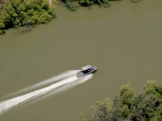 A boat possibly belonging to Customs and Border Protection shoots up the Rio Grande during the team's trip.