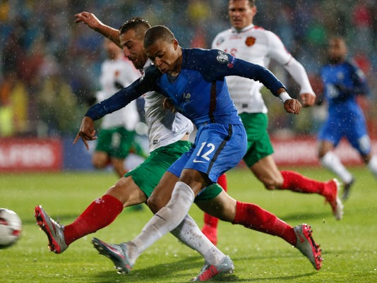France's Kylian Mbappe, front, challenges Bulgaria's Nikolay Boudurov for the ball during the World Cup Group A qualifying soccer match between Bulgaria and France at Vassil Levski Stadium in Sofia, Bulgaria, Saturday Oct. 7, 2017. (AP Photo)