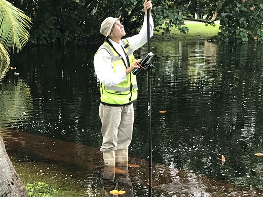 A Martin County engineering worker measures flood waters
