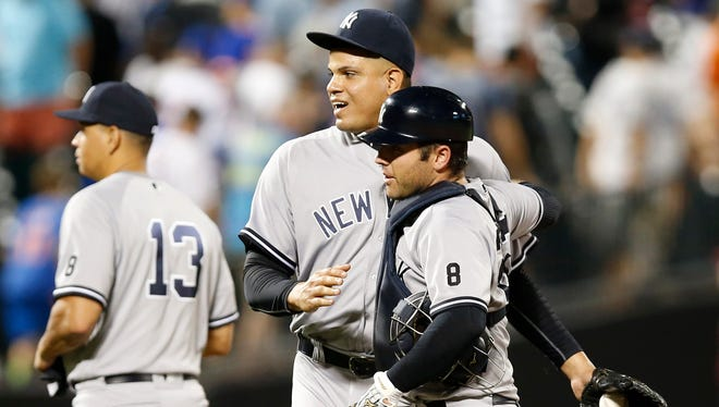 New York Yankees relief pitcher Dellin Betances, center, celebrates with Yankees catcher Austin Romine after the Yankees defeated the Mets 6-5 in the tenth inning of an interleague baseball game between, Monday, Aug. 1, 2016, in New York. New York Yankees Alex Rodriguez (13), who did not play, leaves the field after celebrating with teammates.