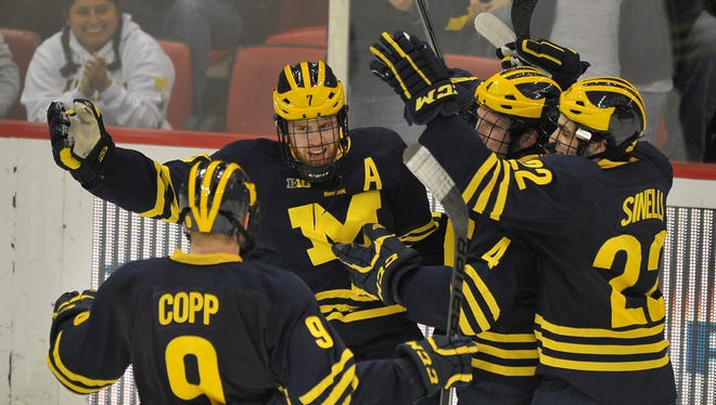 J.T. Compher celebrates with his Michigan teammates after breaking a 1-1 tie in the second period.