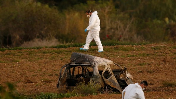Forensic experts walk in a field after a powerful bomb
