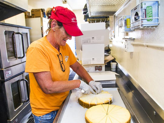 Kim McKee cuts up cheesecake for firefighters battling