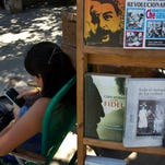 "A book street vendor passes the time on her smart phone as she waits for customers in Havana, Cuba, Tuesday, April 1, 2014. The Obama administration secretly financed a social network in Cuba to stir political unrest and undermine the countryís communist government according to an Associated Press investigation. The project, dubbed ""ZunZuneo,"" slang for a Cuban hummingbirdís tweet, lasted more than two years and drew tens of thousands of subscribers and sought to evade Cubaís stranglehold on the Internet with a primitive social media platform. First, the network would build a Cuban audience, mostly young people; then, the plan was to push them toward dissent.  (AP Photo/Ramon Espinosa) ORG XMIT: WX412"