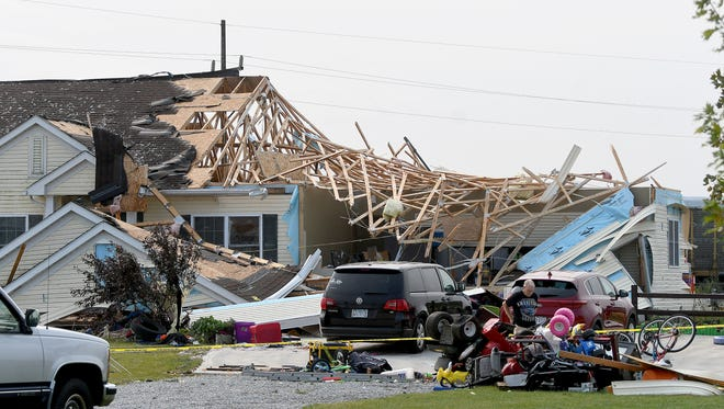 Bill Martin sifts through the personal belongings of his daughter's family after Monday night's storm destroyed a large portion of her family home at 5511 Hook Road in Crestline, Ohio.