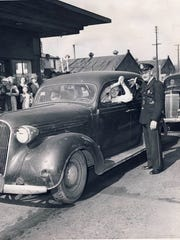 Hugh Cochran becomes the first driver to cross the Louisville Municipal/Clark Bridge for free Nov. 1, 1946 after tolls were eliminated. Bridge Officer F. M. Bennett  waves him on.
