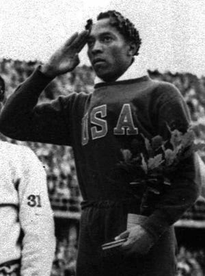 Jesse Owens accepts his long jump gold medal on Aug. 11, 1936.