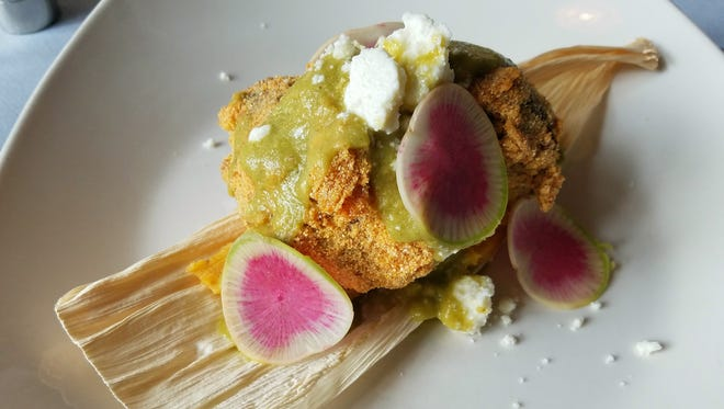 Queso fresco, watermelon radish slices and tomatillo and green chili sauce brighten cornmeal-crusted pork cheeks over a pumpkin tamale at CharBlue, 14 E. Washington St. in Downtown Indianapolis.