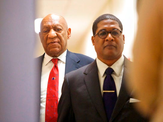 Actor and comedian Bill Cosby, left, reacts after being