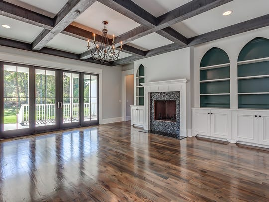 A dark, moody color in the back of the bookcases accentuates the gothic arches while soft black french doors frame the exterior view.