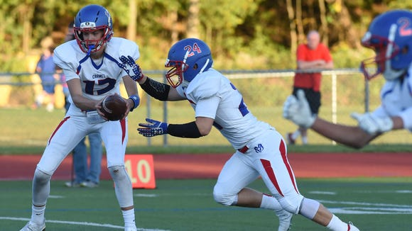 Carmel's Peyton Cayea, left, hands off to teammate Sam Duke, right, during Friday's game against Arlington.